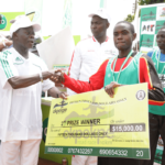 Edo Governor Adams Oshiomhole presents a cheque to Timothy Toroitich from Uganda, 2nd prize winner with time of 29 mins, 44 seconds at the Okpekpe Road Race 10km.