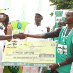 Edo Governor Adams Oshiomhole presents a cheque to Yusuf Biwott, 3rd prize winner with time of 29 mins 50 seconds at the Okpekpe Road Race 10km.