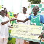 Edo Governor Adams Oshiomhole presents a cheque to Kenyan Moses Masai, Winner with time of 29 mins & 39 seconds at the Okpekpe Road Race 10km.